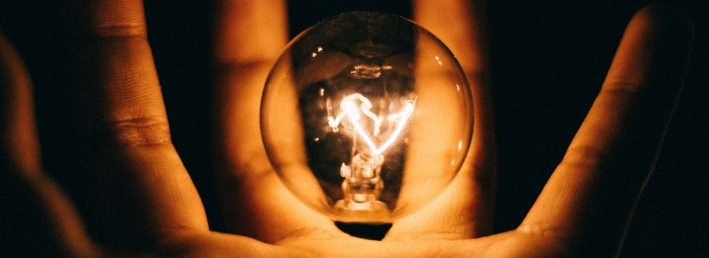 Hand holding a lit lightbulb | Kings Patent & Trade Marks Attorneys